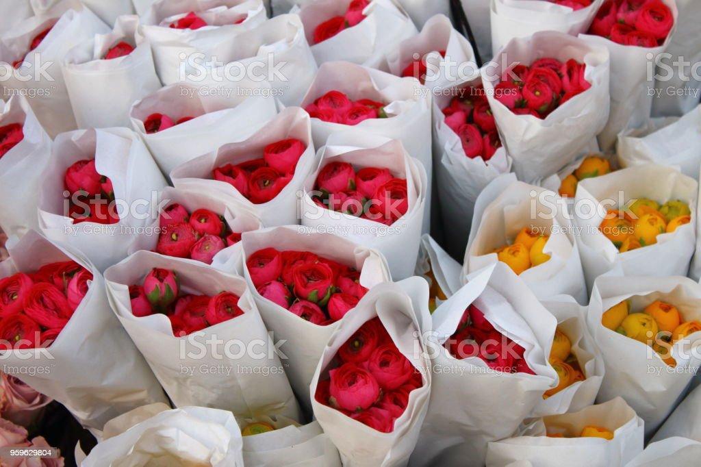 Ramo de flores de color rojo y amarillo ranúnculo envuelto en papel - Foto de stock de Adulto libre de derechos