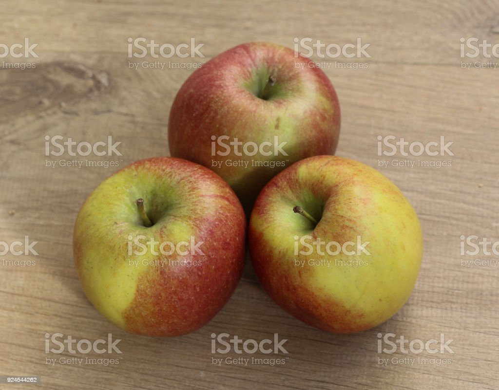 Red and yellow fresh braeburn apples on wooden background stock photo