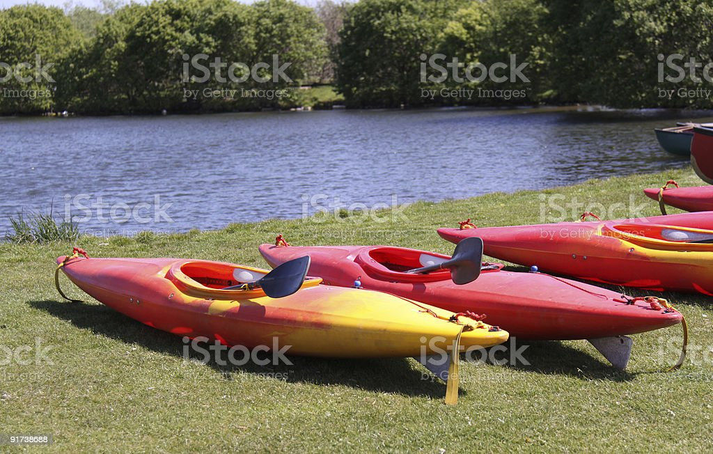 Red and yellow kyaks moored beside a lake royalty-free stock photo