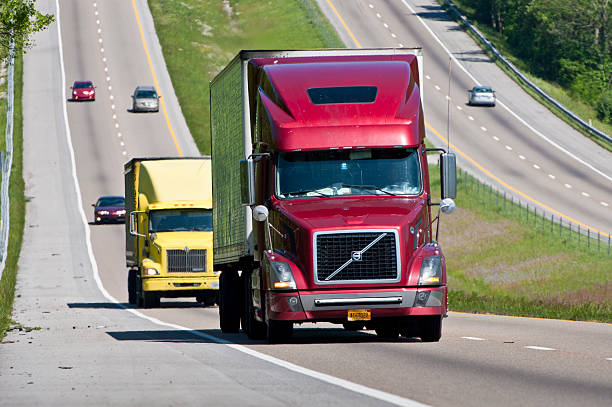 red and yellow semi trucks climb hill on interstate - volvo trucks bildbanksfoton och bilder