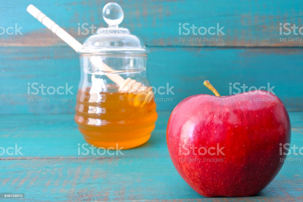 Red apple and honey jar on a turquoise background stock photo