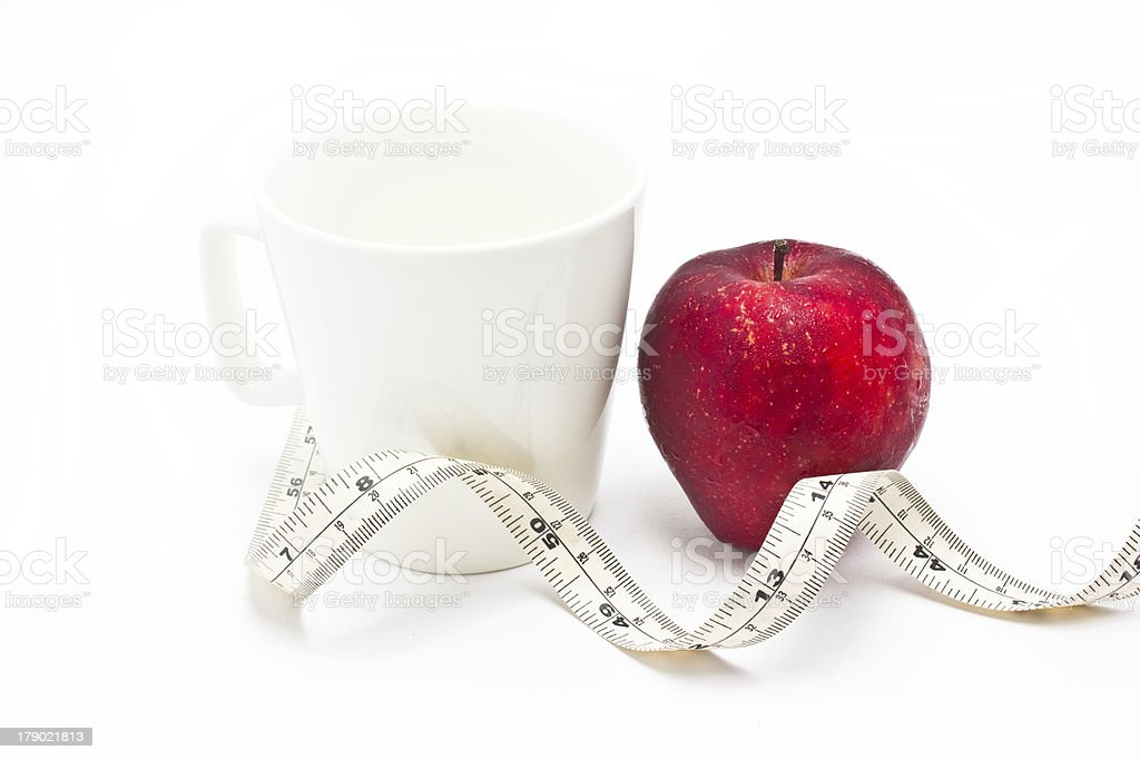 Red apple and measure tape with white ceramic glass. stock photo