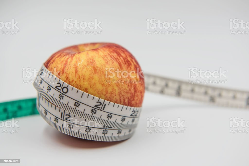 Red apple and Measuring tape wrapped around on white background royalty-free stock photo