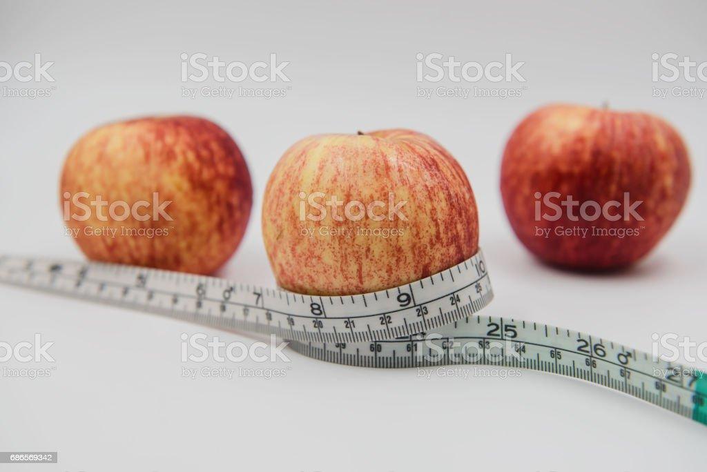 Pomme rouge et mètre ruban enroulé autour sur fond blanc photo libre de droits