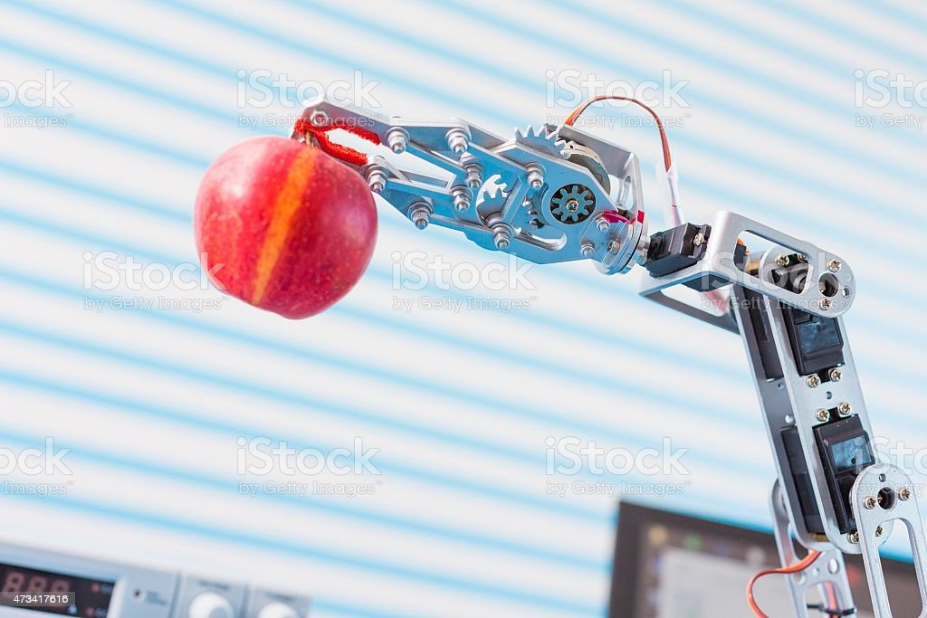 red apple in a  robot  arm stock photo