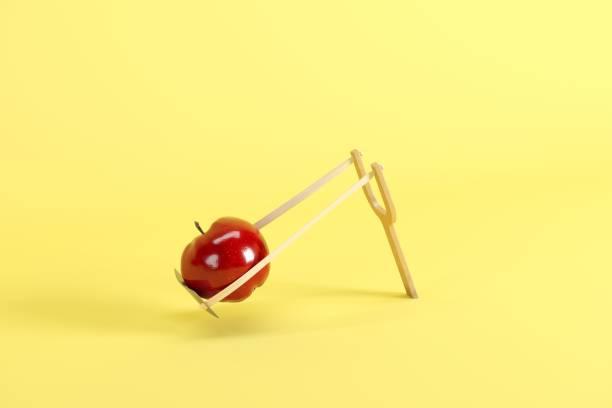Roter Apfel in einem Schleuder auf gelbem Hintergrund. Minimales Fruchtgedankkonzept. – Foto