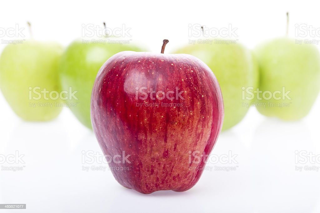 red apple in front of green ones as a triangle royalty-free stock photo