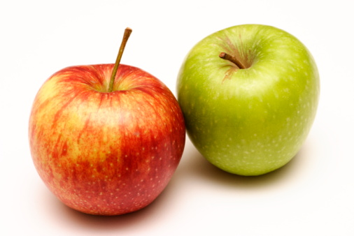 A red apple next to a green apple on a white background