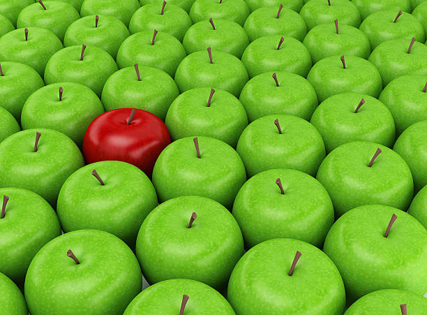red apple on a background of green apples - single object stock pictures, royalty-free photos & images