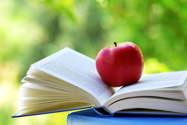 red apple on a book stock photo