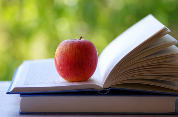 A red apple on a open book stock photo