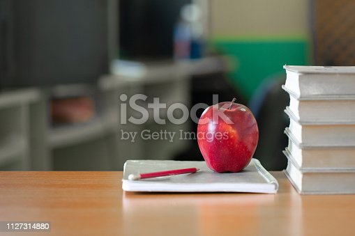 istock Red apple on a pile of books, paper and pencil on the desk, Educational concept. 1127314880