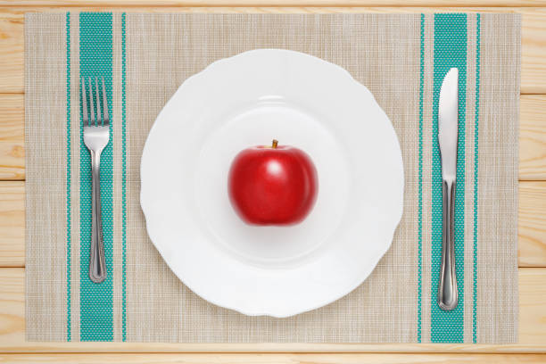 red apple on a white plate red apple on a white plate on the table with a knife and fork antihistamine stock pictures, royalty-free photos & images