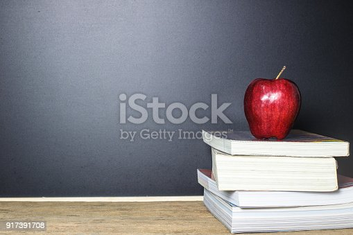 istock Red apple on book with Blackboard (Chalk Board) as background on wood table. Education concept. 917391708