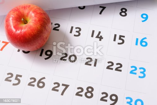 High angle view of red apple on calendar.