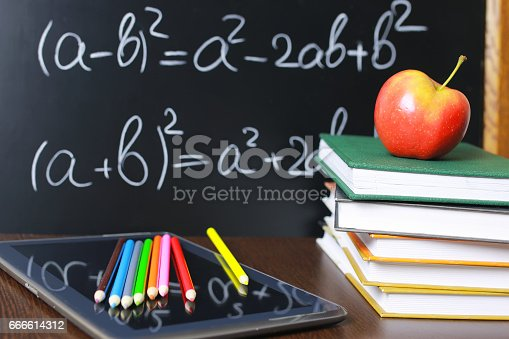 istock red apple on notebook with book stack 666614312