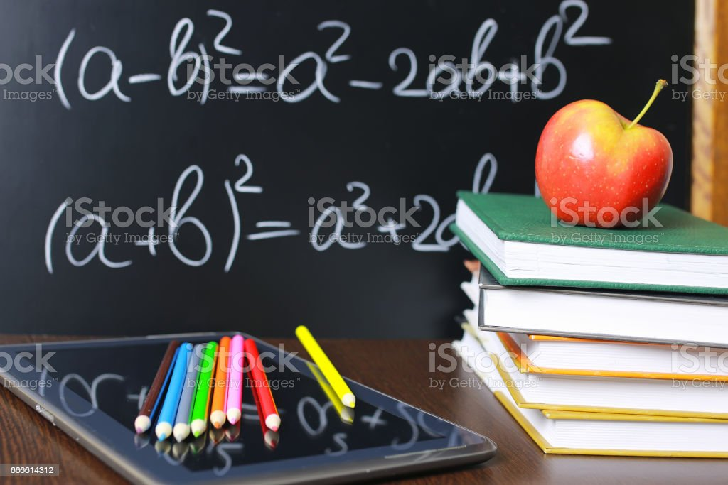 red apple on notebook with book stack stock photo