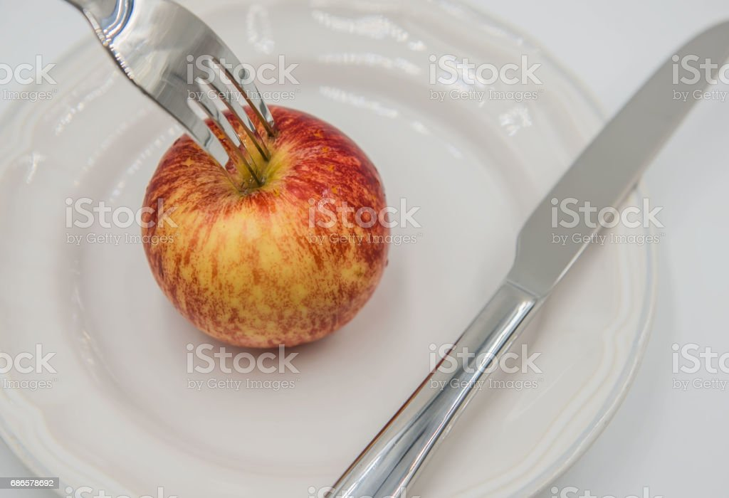 Red apple on plate and fork , knife  on white background foto stock royalty-free