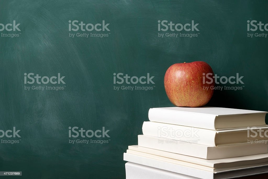 Red apple on stacked blank books in front of blackboard royalty-free stock photo