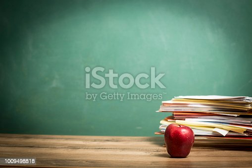881192038 istock photo Red apple, papers stack on wooden school desk with chalkboard. 1009498818