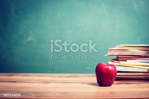 881192038 istock photo Red apple, papers stack on wooden school desk with chalkboard. 1021174224