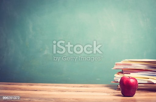 881192038 istock photo Red apple, papers stack on wooden school desk with chalkboard. 996251372