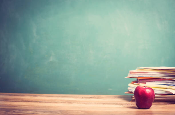 Roter Apfel, Stapel Papiere auf hölzernen Schulbank mit Tafel. – Foto