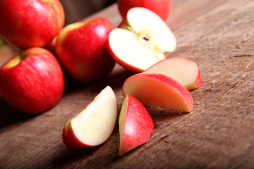 Red Apple and slices on barn Wood