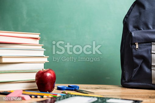 istock Red apple, school supplies on wooden desk with chalkboard. 1021174588
