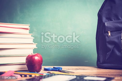 istock Red apple, school supplies on wooden desk with chalkboard. 1154081887