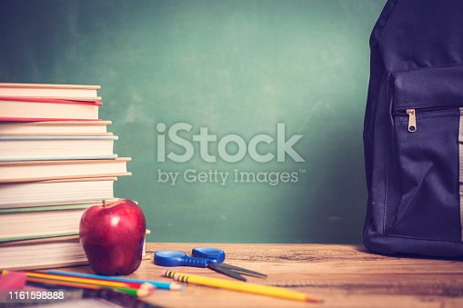 istock Red apple, school supplies on wooden desk with chalkboard. 1161598888