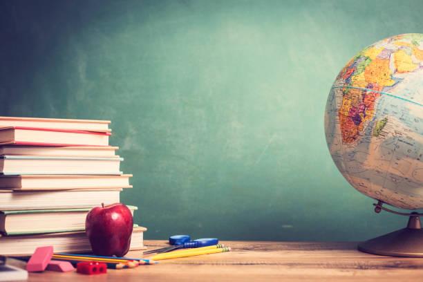 Roter Apfel, Schulmaterial auf hölzernen Schreibtisch mit Globe, Tafel. – Foto