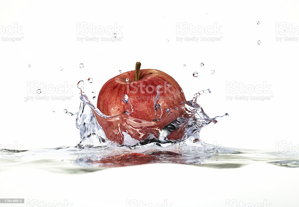 Red apple splashing into water. Close-up side view. stock photo