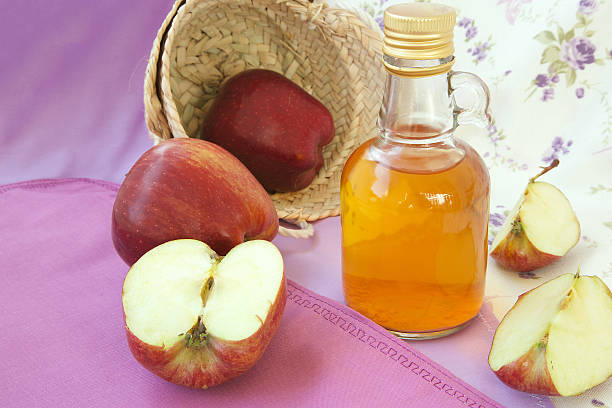 Red apple vinegar A glass bottle of red apple vinegar. Fresh red apples in the background. apple cider vinegar stock pictures, royalty-free photos & images