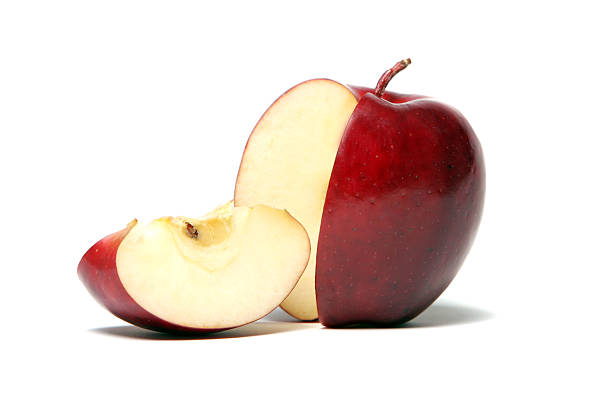 A red apple with a cut slice on a white background stock photo