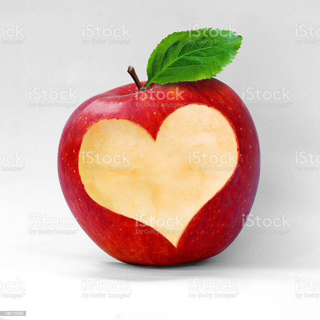 Red apple with a heart shaped cut-out. stock photo