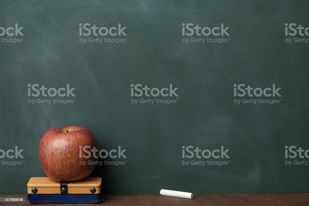 Red apple with eraser and chalk in front of blackboard royalty-free stock photo