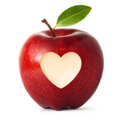 A shiny fresh red apple with heart shape carved symbol and green leaf, isolated on white background.