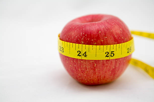 red apple with tape measure stock photo