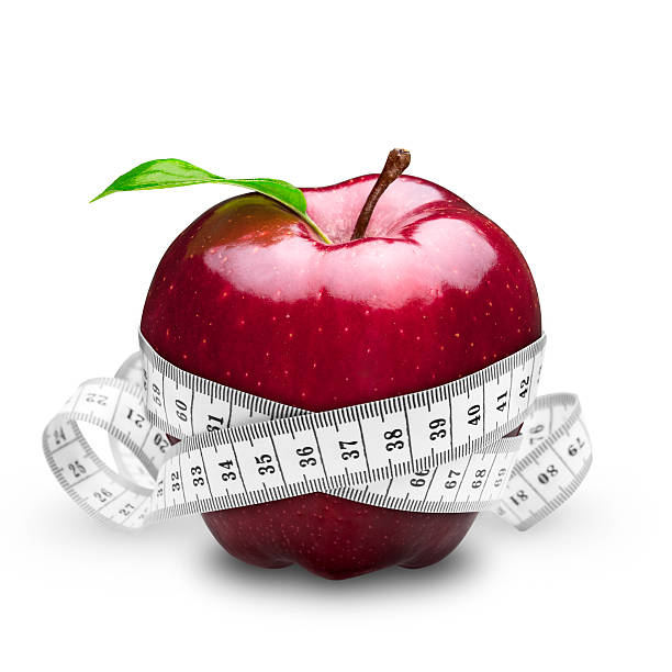 Red apple with white tape measure wrapped around it stock photo