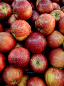 A lot of red apples. Abstract background. Seasonal fruits on local market.