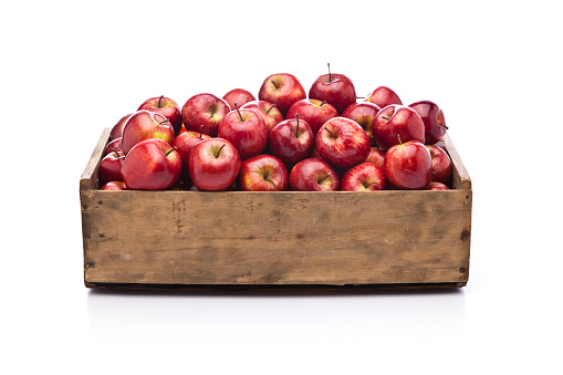 Red apples in a wooden crate isolated on white background