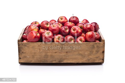 istock Red apples in a wooden crate isolated on white background 487224702