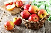 赤いリンゴの木製の背景にグレーのバスケット