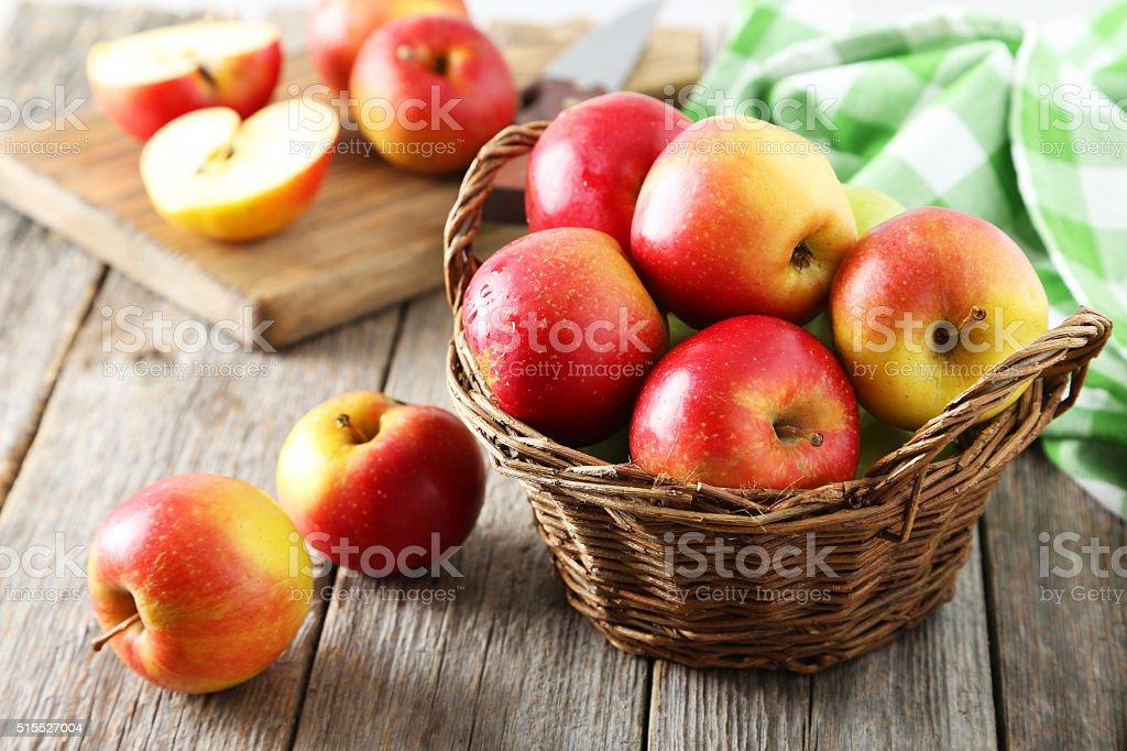 Red apples in basket on grey wooden background bildbanksfoto