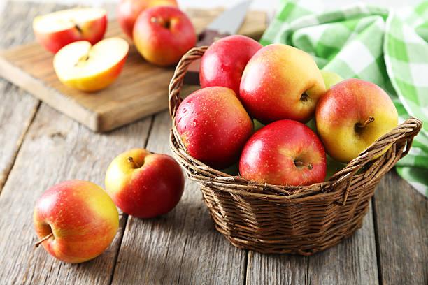 赤いリンゴの木製の背景にグレーのバスケット ストックフォト