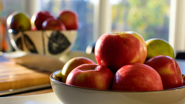 Red apples in bowl in sunny kitchen in autumn stock photo