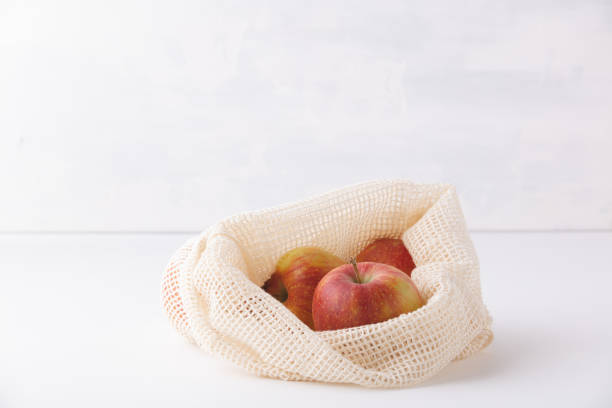 Red apples in reusable cotton bags. Copyspace stock photo