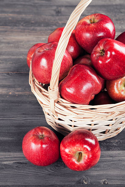 Red apples in the basket Fresh red apples in a wicker basket red delicious apple stock pictures, royalty-free photos & images