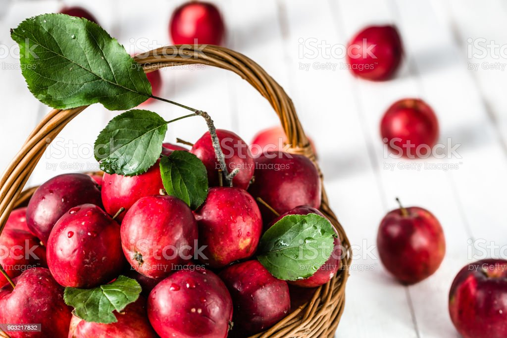 Red apples on table in the basket, pile of fresh apple fruit on white background stock photo